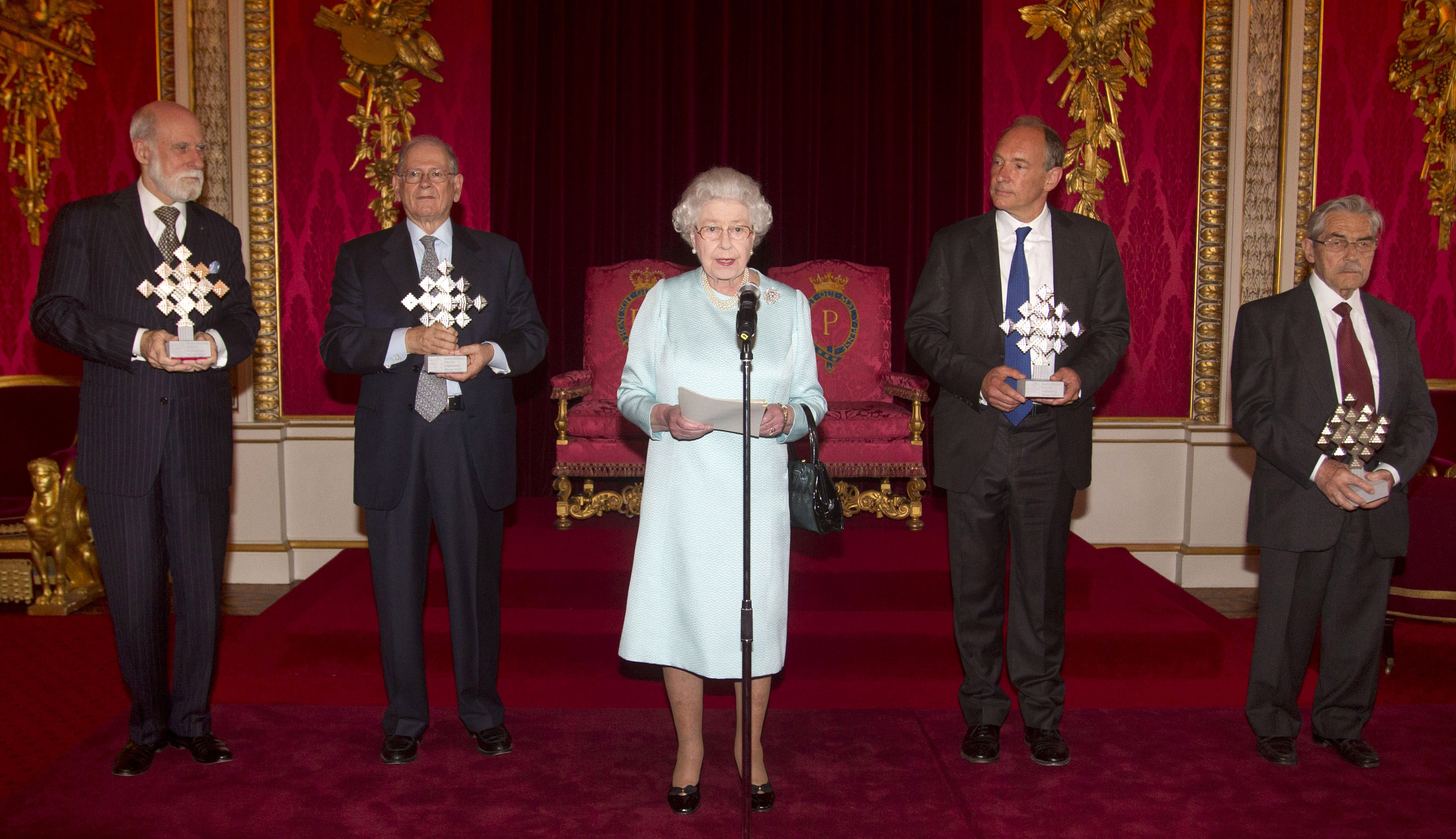 IMAGE DISTRIBUTED FOR QUEEN ELIZABETH PRIZE FOR ENGINEERING - Britain's Queen Elizabeth II speaks in front of the winners of the Queen Elizabeth Prize for Engineering (QEPrize) at Buckingham Palace, London, on Tuesday, June 25, 2013. The five prize winners were the leading lights in the creation of the Internet and the world wide web. Pictured from left; Vint Cerf, Robert Kahn, Tim Berners-Lee and Louis Pouzin hold their awards. US engineer Marc Andreesen was unable to attend the prize giving. The Queen Elizabeth Prize for Engineering (QEPrize) is a new global engineering prize rewarding and celebrating an individual or group responsible for a ground-breaking innovation in engineering that has been of global benefit to humanity. The winners share the 1 million pound (US$1.6 million or 1.16 million euro) prize money. (Lewis Whyld/QEPrize via AP Images)