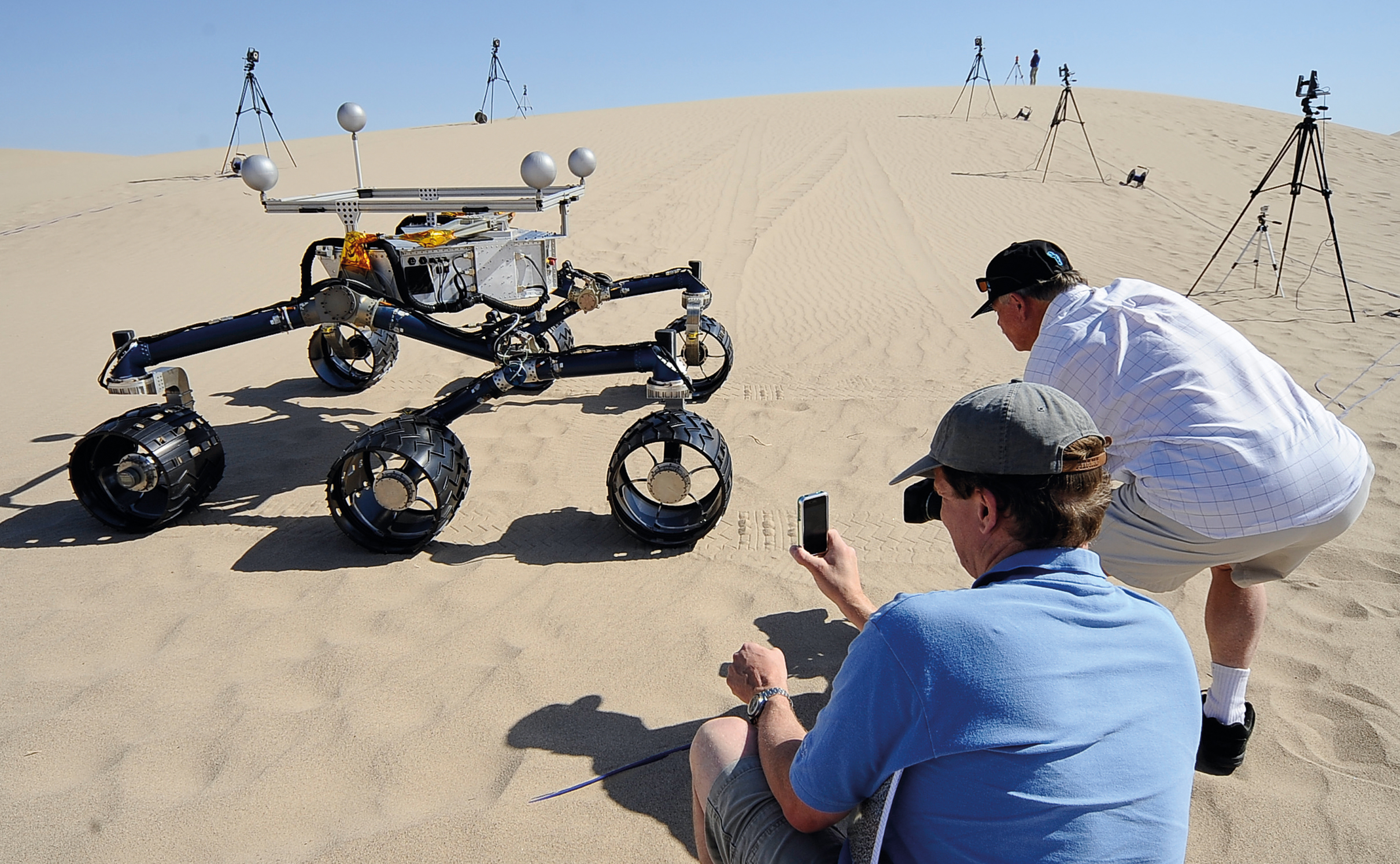 """10 May 2012, Baker, California, USA ---  Members of the Mars Science Laboratory/ Curiosity team including rover drivers and scientists tests out  an engineering model of its next generation Mars rover dubbed """"Curiosity"""" in the Dumont Dunes near Baker, California May 10, 2012.  --- Image by © Gene Blevins/ /Corbis"""