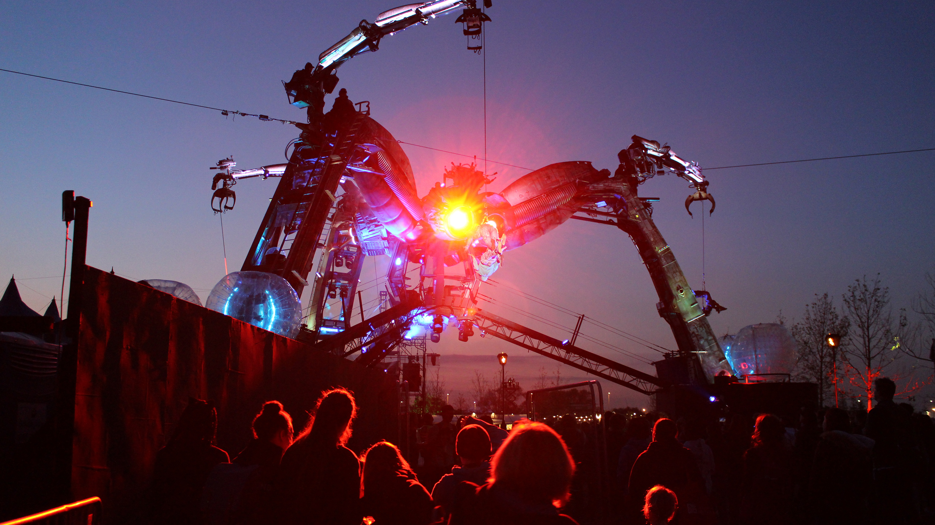 Image of a crowd gathering around the large Arcadia Spider while lights shine from its head.