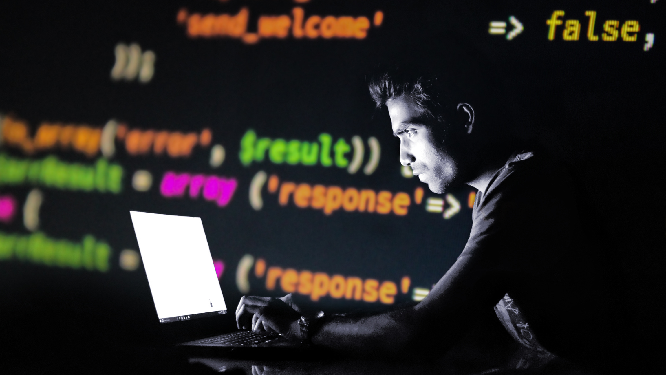 Image of a hacker in a dark room. Code is displayed in the background.