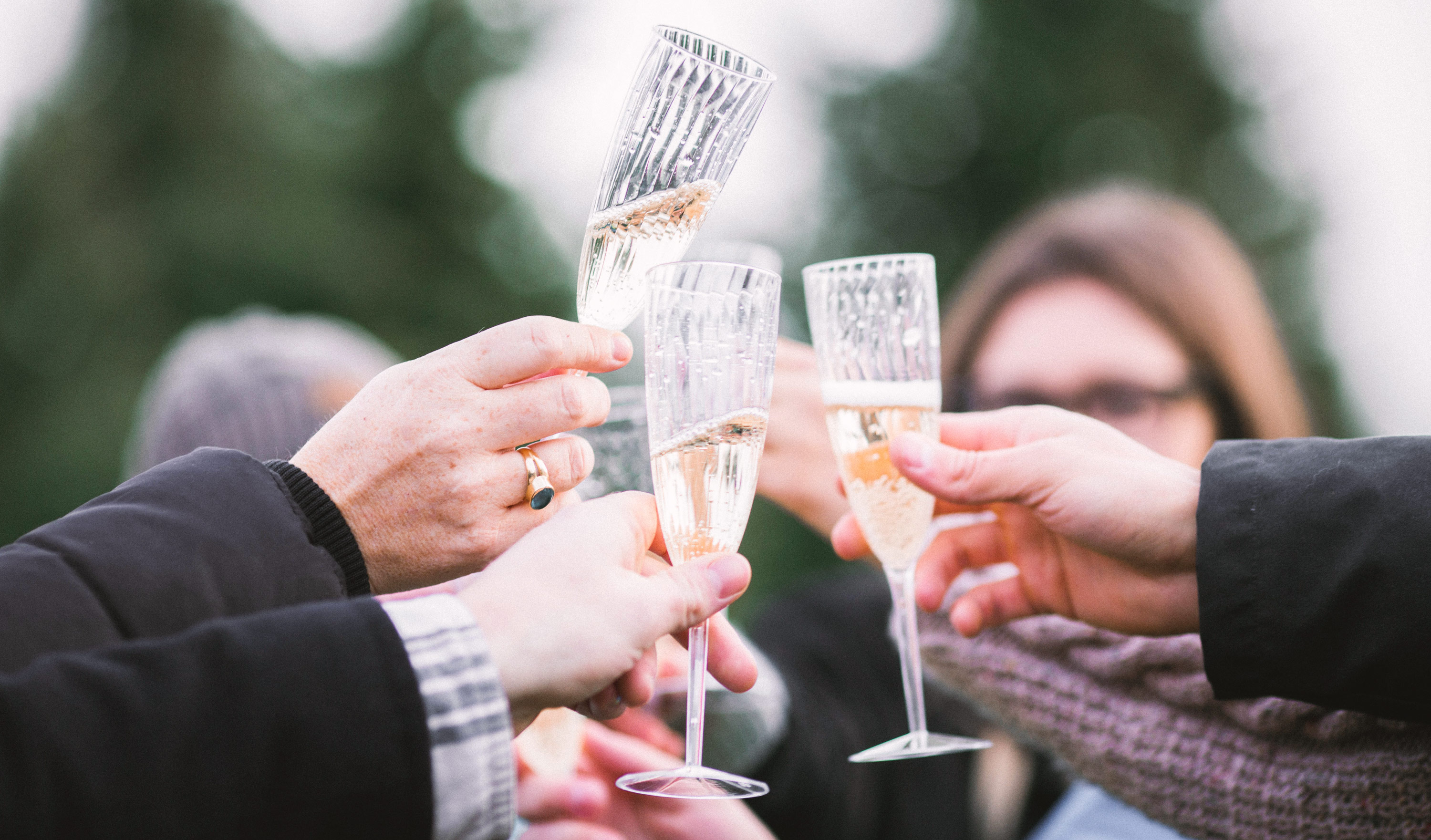 Image of people raising a glass of champagne in celebration