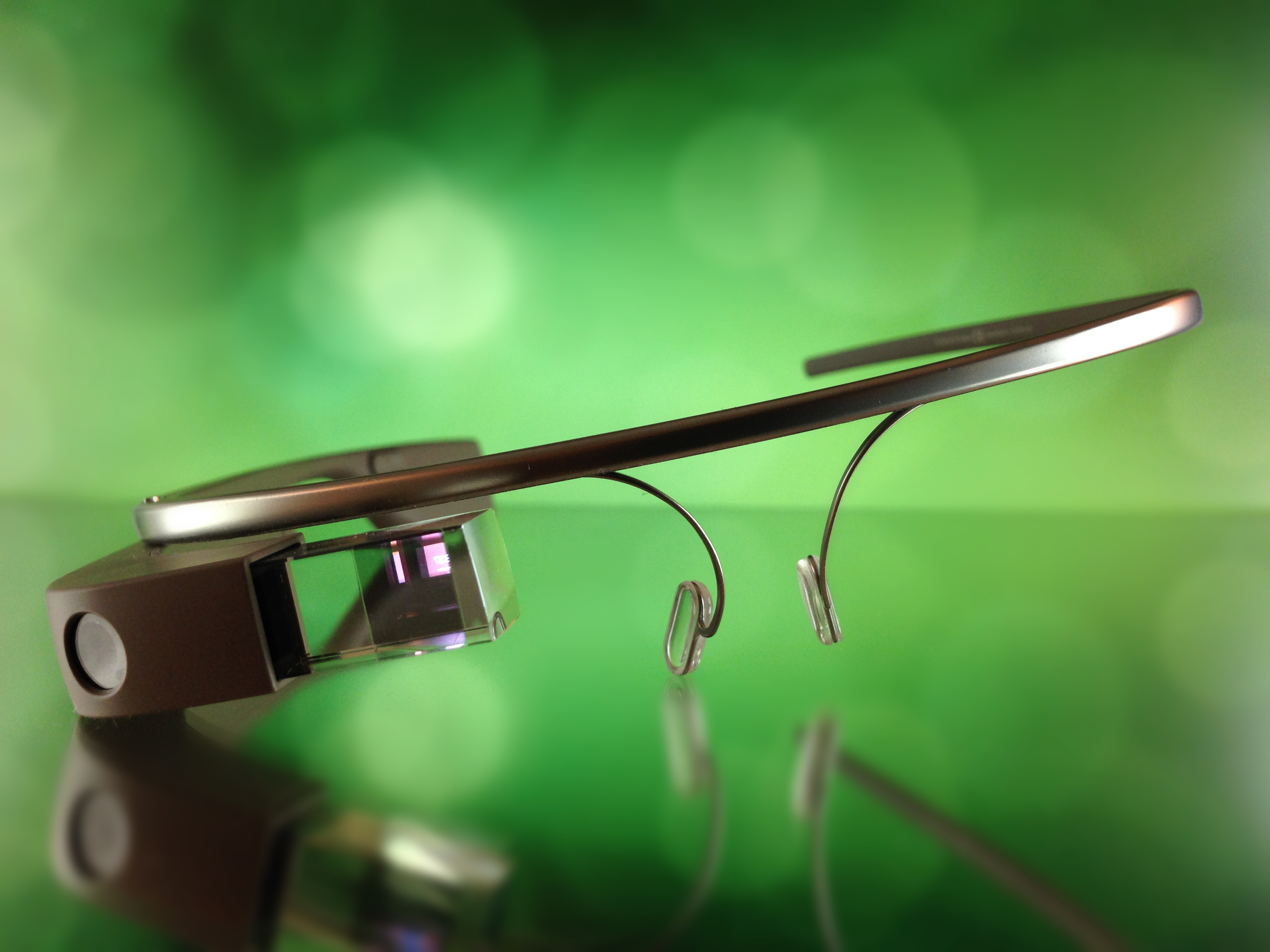 Image of Google Glass on a clear surface with a blurred green background