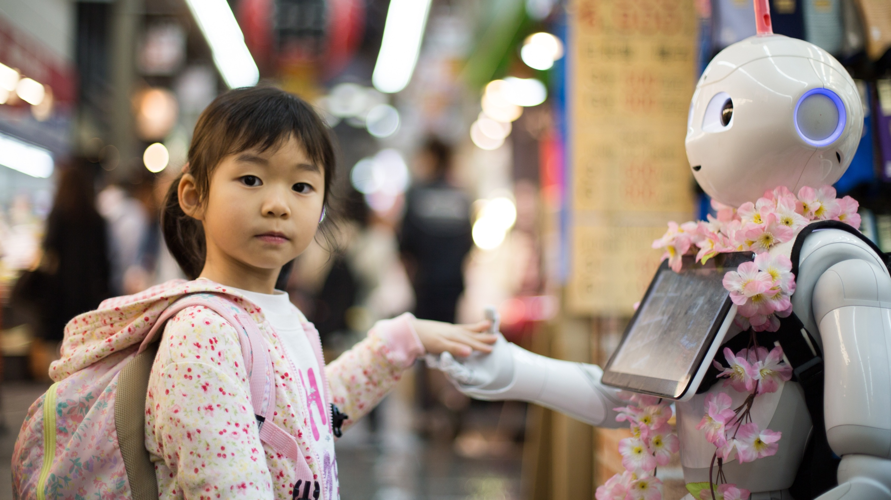 Image of a young girl holding the hand of a robot.