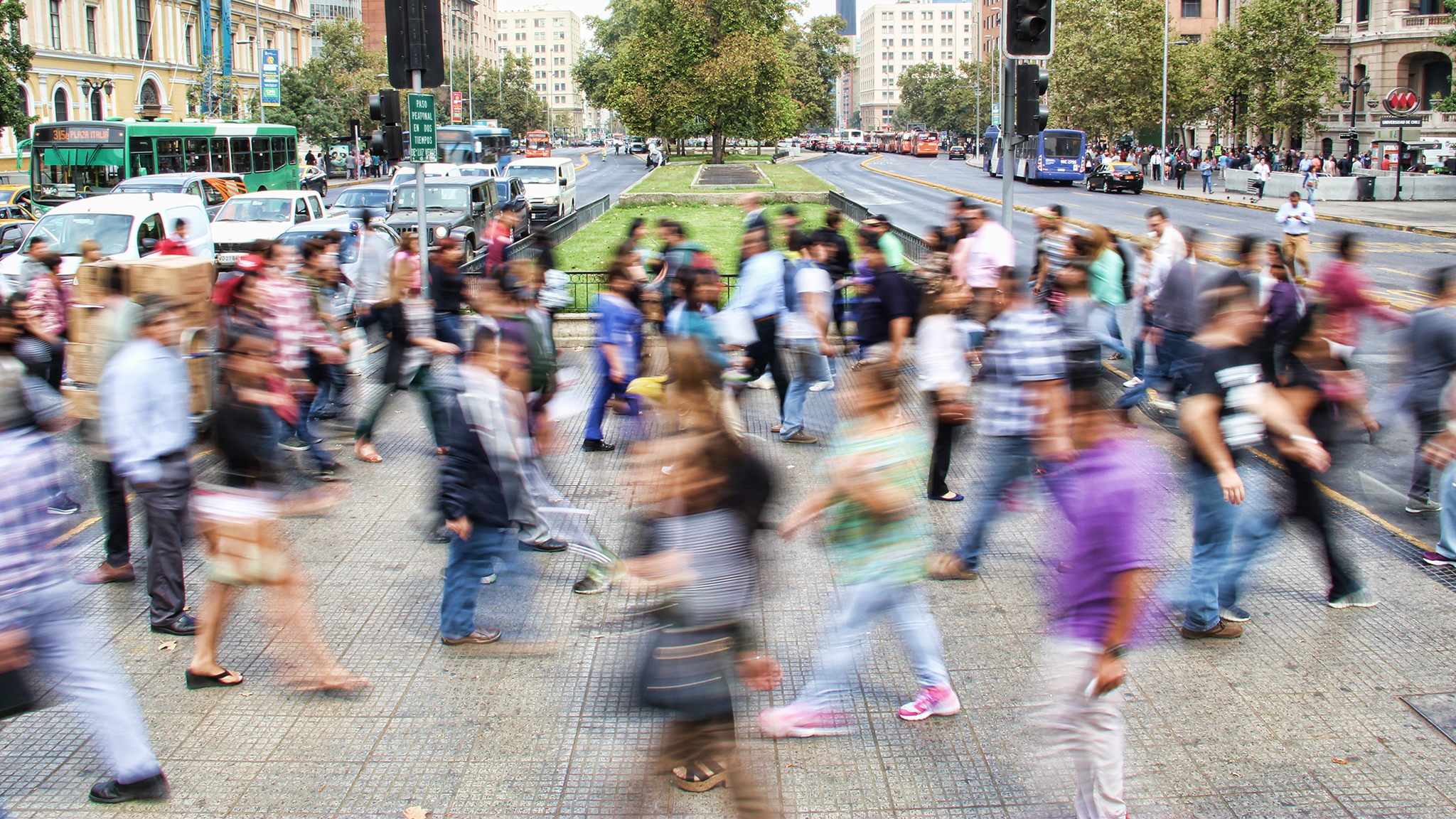 Motion-blur image of people walking both ways over a walkway during the day.