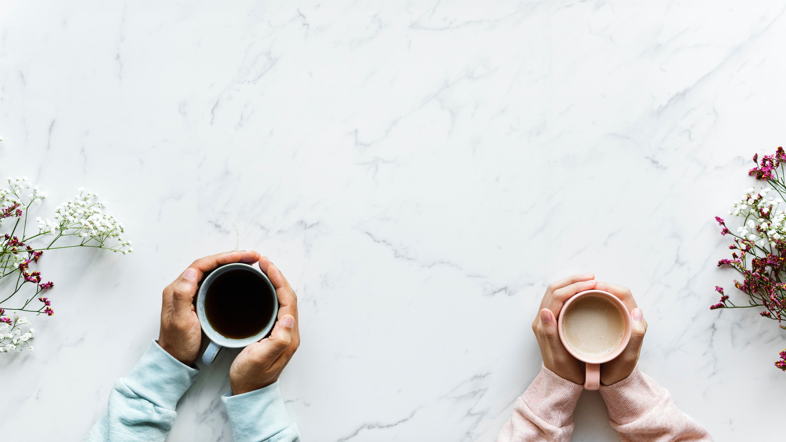 Image taken directly above of two people's hands, one man and one woman, holding their coffees over a white marble counter.