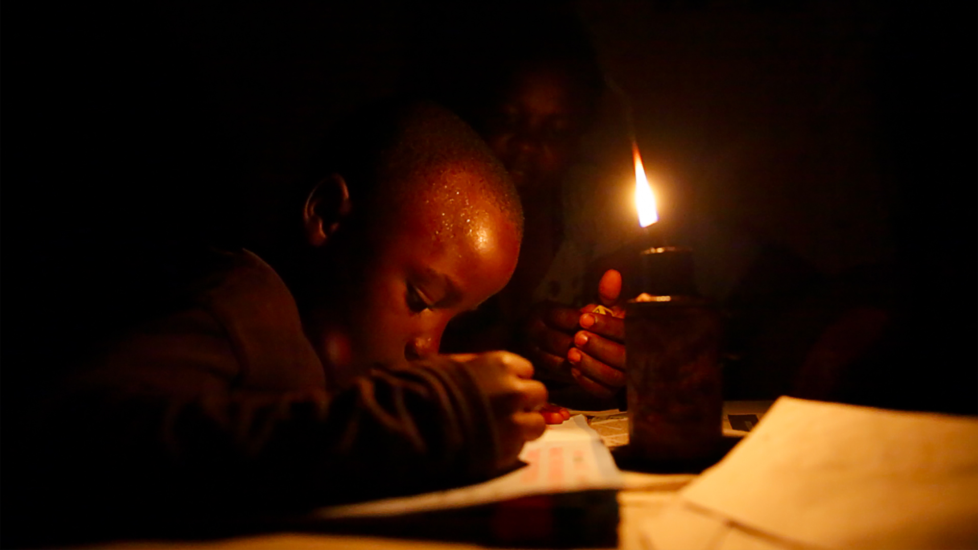 Image of a boy reading using the light of a kerosene lamp.