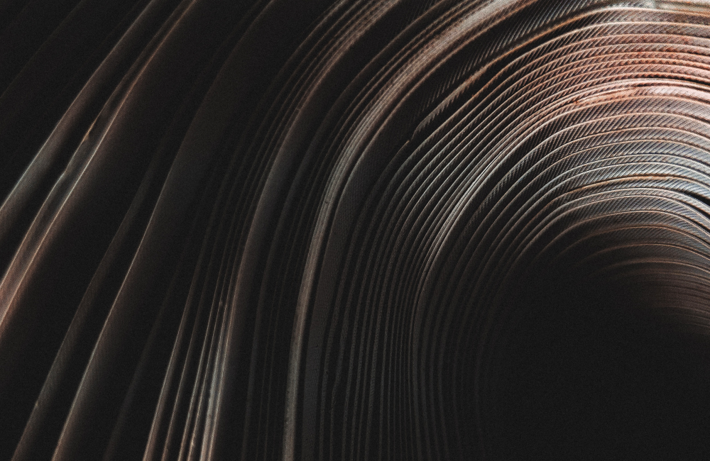 Abstract: a course material twirling around a dark center in the bottom right corner of the image.