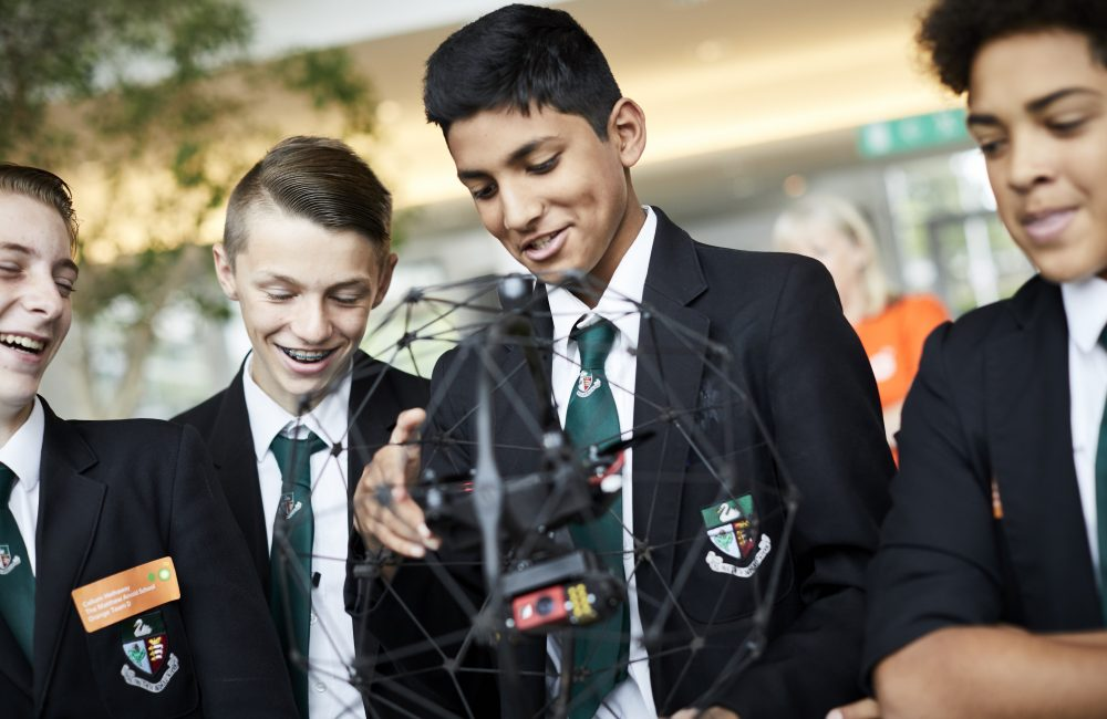 Students examine a drone within a spherical structure at BP's STEM education day