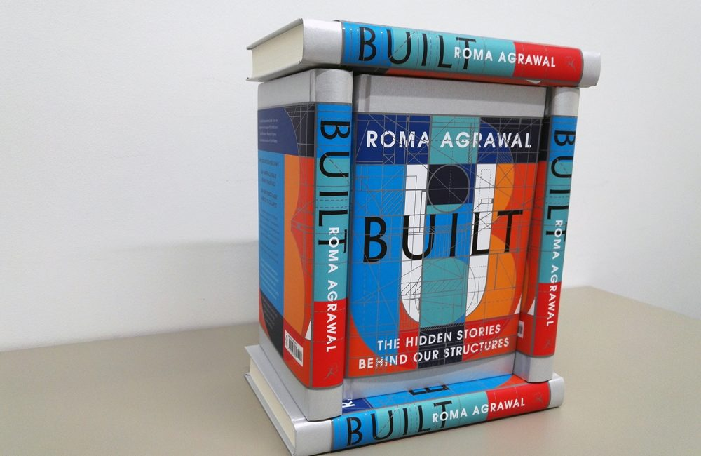 Copies of the 'BUILT' book is stacked up and arranged to look like a building.