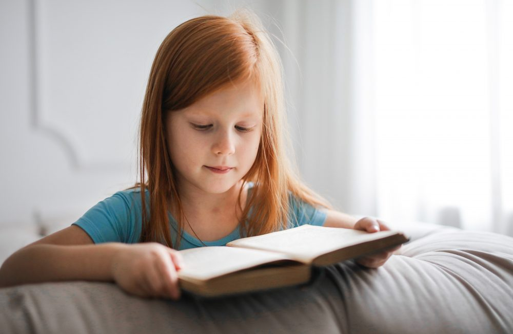 A girl with red hair is wearing a blue t-shirt and reading a book.