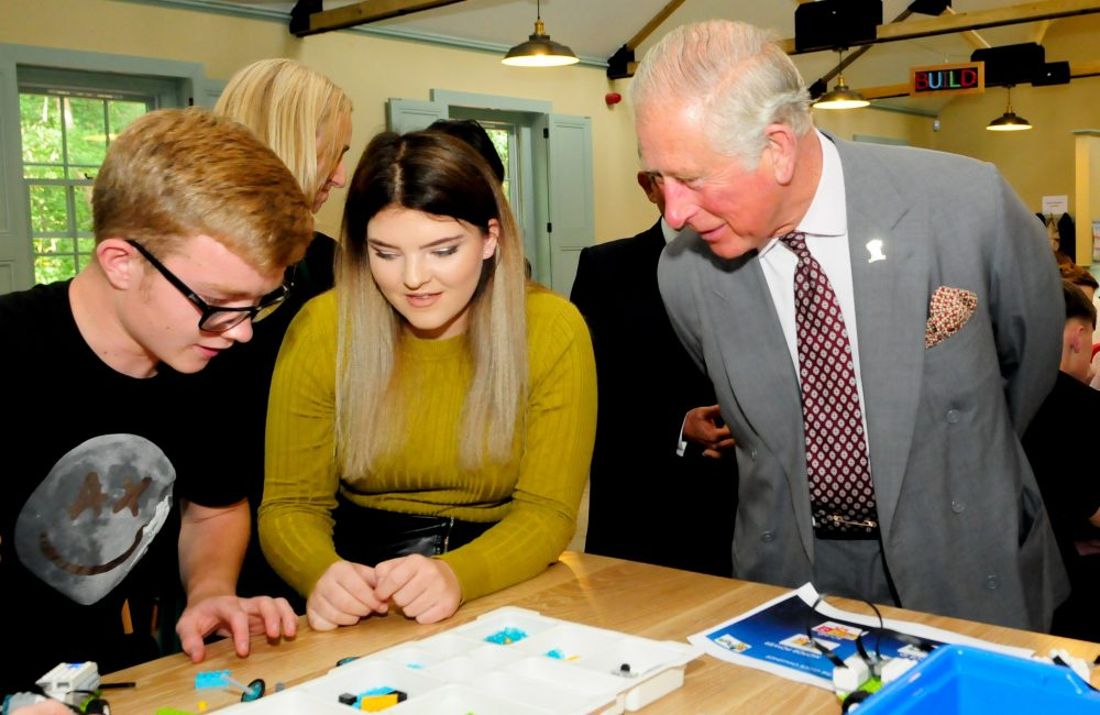 HRH The Prince of Wales reviews the work of the attending high school students at Dumfries House.