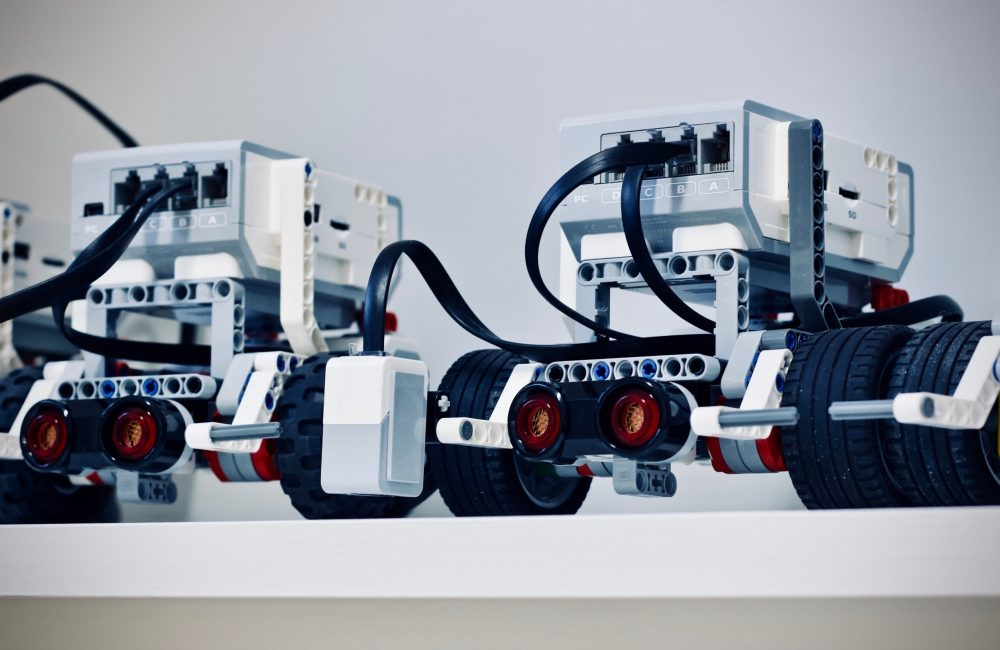Three identical robots, with wheels, side by side on a shelf. The dominant colours of the image are white, black, and grey. The robots have some components with red and yellow.