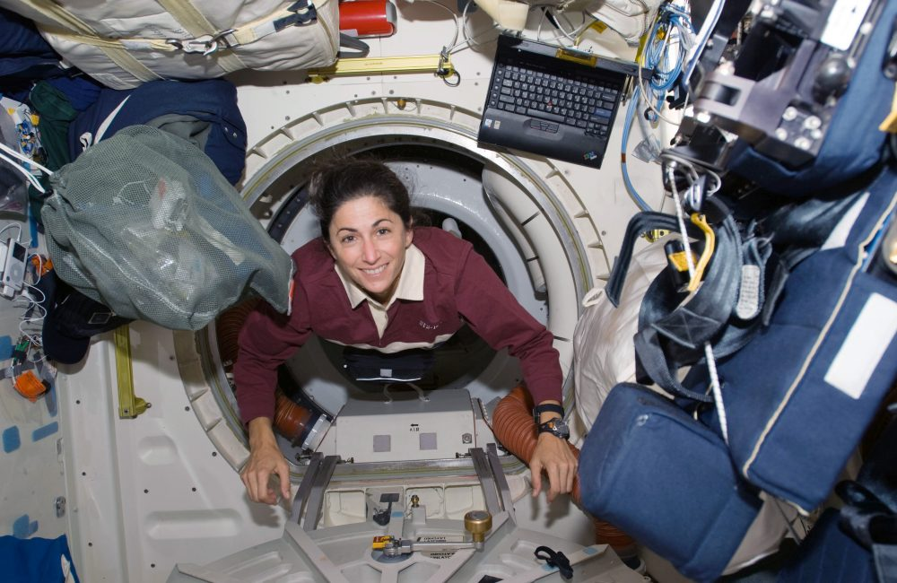 Astronaut Nicole Stott looks up at the camera from inside a spacecraft