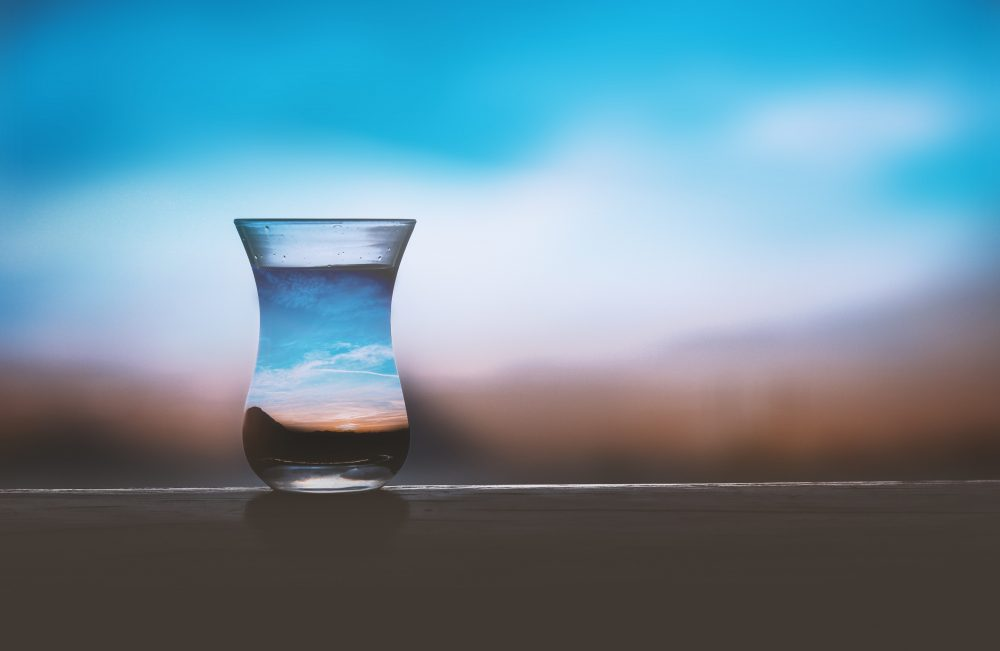 Water glass on a wall in front of a blurred landscape.