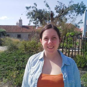 Jessica Middlemiss smiles at the camera in front of a house with a big garden