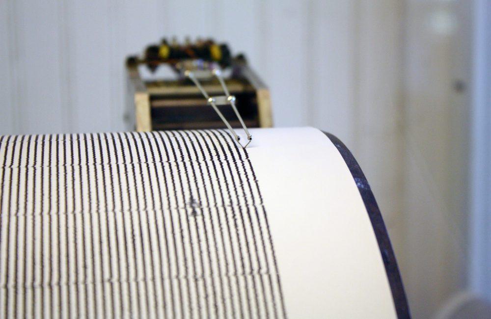 A seismograph recording quakes on a long piece of 'paper'
