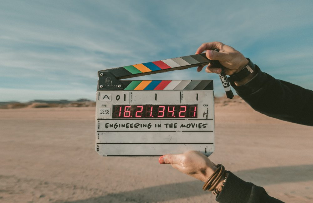 """A person holds out a clapperboard to start a film. The production title on the board reads: """"Engineering in the movies"""""""